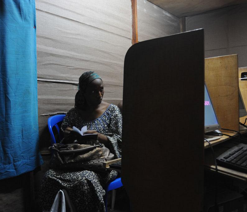 Kadie fait ses comptes en fin de journée dans le cyber café qu'elle a ouvert pour financer ses études. En DEA, elle a investi sa bourse d'étude dans ce business qui lui rapporte 0/mois. Si elle ne réussit pas les concours de al fonction publique, elle investira dans une plantation d'hévéa. © Joan Bardeletti