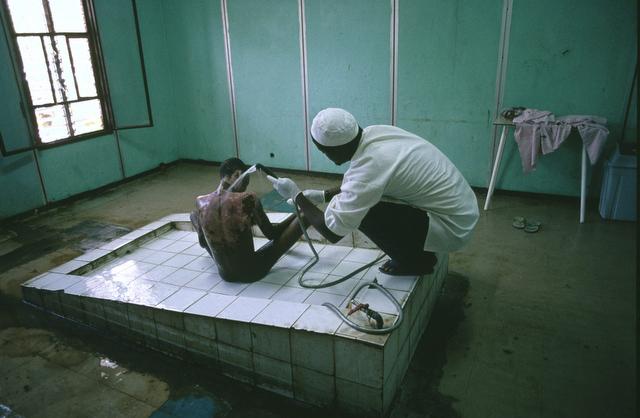 © Pascal Maitre / Cosmos for Geo # 008 Somalie, octobre 2002. Mogadiscio. Un grand brûlé est soigné par jet d'eau à l'hôpital Madina. Il a été brûlé par de l'essence. Il n'y a pas de pompe dans la capitale, et le carburant est distribué dans des petits bidons en plastique, ce qui provoque beaucoup d'accidents comme celui-ci.