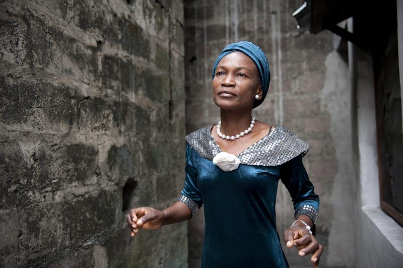 Pauline Diasonama est choriste dans l'Orchestre Symphonique Kimbanguiste. Pour gagner sa vie, elle vend des fleurs artificielles sur le trottoir d'une avenue de Ngiri Ngiri à Kinshasa. Sur la photo, elle pose devant chez elle, un petit appartement installé dans un immeuble inachevé - 19/06/2009 - KINSHASA, RDC © Vincent Boisot