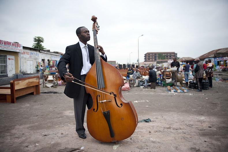 Edgard Mbidiamanbu-Lelo (30 ans) est chef de pupitre contre basse dans l'Orchestre Symphonique Kimbanguiste à Kinhasa. Diplômé en économie, il est actuellement au chômage. Sur la photo, il pose avec son instrument dans une rue proche du lieu de répétition - 26/06/2009 - KINSHASA, RDC © Vincent Boisot