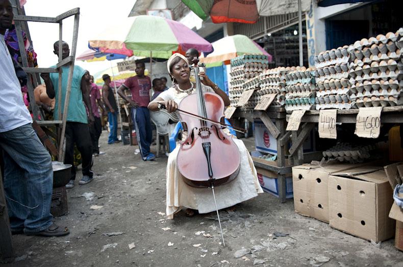 Josephine Msimba-Mpongo (37 ans, mariée, 1 enfant), est violoncelliste dans l'Orchestre Symphonique Kimbanguiste à Kinshasa. Pour gagner sa vie, elle vend des oeufs sur sur le marché central de Kinshasa. Sur la photo, elle pose devant sur son lieu de travail avec son instrument - 26/06/2009 - KINSHASA, RDC © Vincent Boisot