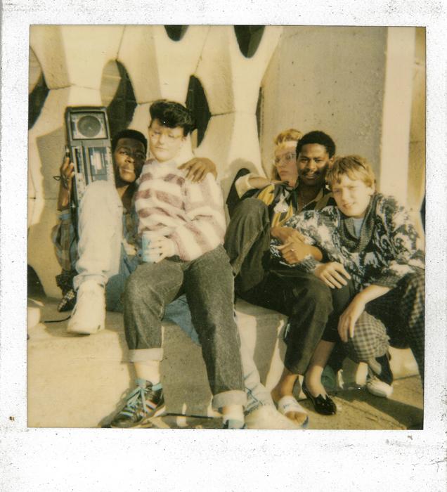 Lucio ANADE (2nd à partir de la droite) à 19 ans avec sa bande d'amis en Allemagne de l'Est. Derrière lui, Diana sa copine et à guache, son ex. © Joan Bardeletti