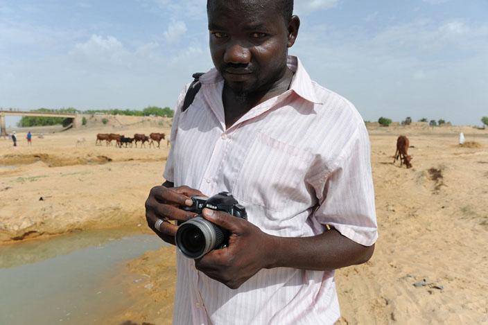 Abdoulaye Barry est en train de réaliser des prises de vues dans le lit du fleuve Chari près du pont de Chagoua à N'Djaména. © Philippe Guionie/Myop