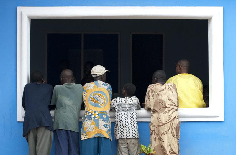 Le palais d'Otuam. Les villageois, appuyés à la fenêtre, écoutent et observent les audiences public que donne King Peggy. © Sarah Preston