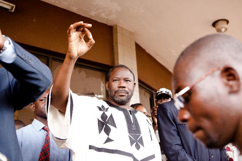 Le Professeur Albert Ouédraogo, ministre de l'Enseignement, tente de calmer les élèves devant l'entrée de son ministère, saccagée une heure avant. © Sophie Garcia