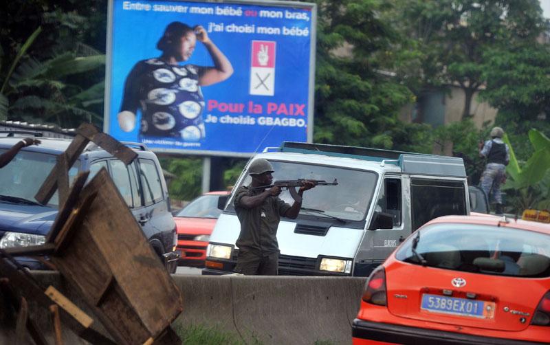 Un militaire fidele au président sortant Laurent Gbagbo vise des supporters du président elu Alassane Ouattara lors d'un manifestation le 11 février 2011 a ABidjan. © Issouf Sanogo