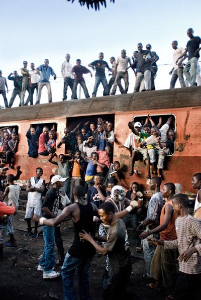 Le cortège de Six bolites, dans le quartier de Massina, rencontre un train. Avant chaque compétition, les catcheurs défilent avec un orchestre pour drainer la foule vers le lieu du combat. © Colin Delfosse