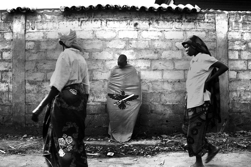 Sarcophage ou emballage législatif - Photo prise d'une voiture. Militant du CNDD (parti au pouvoir au Burundi) rencontré après le dernier meeting avant les législatives 2010 au Burundi, adossé à mur en plein Bujumbura. Ces élections se terminent par une victoire écrasante du CNDD et un boycott des partis de l'opposition. Un emballage du parlement avec une majorité à plus de 2/3. © Teddy Mazina