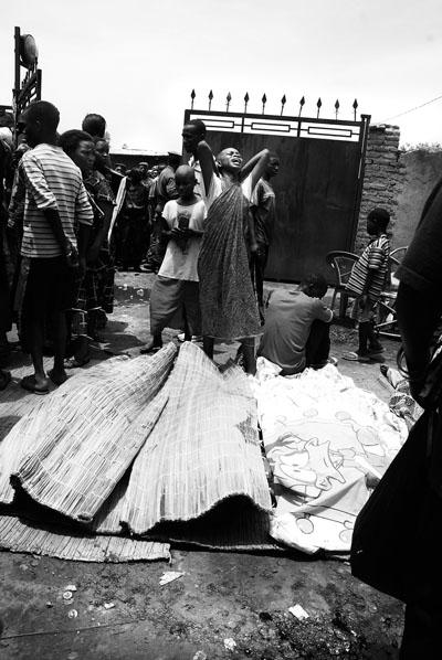 La douleur - Une jeune fille hurlant de douleur sa mère est morte et emballée dans l'une des nattes sur le sol souillé de sang dans la natte une des victimes du massacre de Gatumba le 19 septembre 2011 © Teddy Mazina