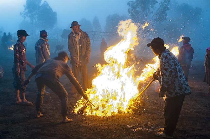 Dans un abattoir, les gens brûlent un cochon afin d'en éliminer rapidement les poils. C'est une occasion pour se réchauffer autour d'un feu. Le RN 7 traverse la region la plus froide de Madagascar où la température peut descendre à 5 ° en hiver. © Rindra Ramasomanana
