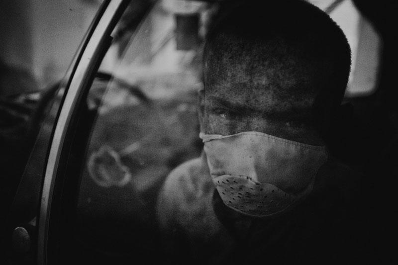 Les enfants de la lune : Yacine portant un masque de protection, attandant son pére dans la voiture il a arreté l école a cause de la maladie. © 2014 - Zied Ben Romdhane